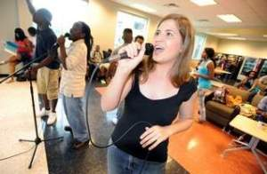 First-year student Emily Heflin sings karaoke with other students between classes at the student center at BPCC on Thursday. (Douglas Collier/The Times)