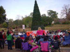 Festival attendees sit around the Christmas centerpiece on the Riverfront